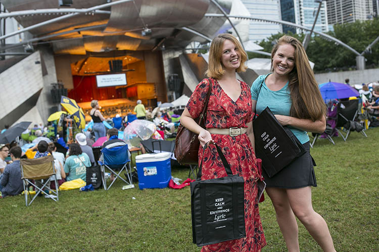 Stars of Lyric Opera at Millennium Park - Audience members hold bags that say Keep Calm and Experience Lyric on the lawn of the Jay Pritzker Pavilion in Chicago.