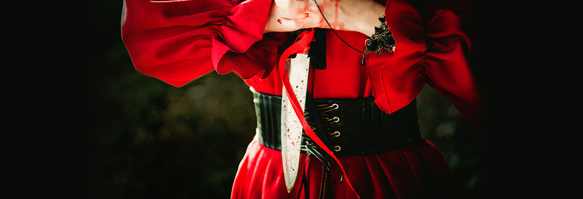 A woman in a red dress holding a bloody dagger.