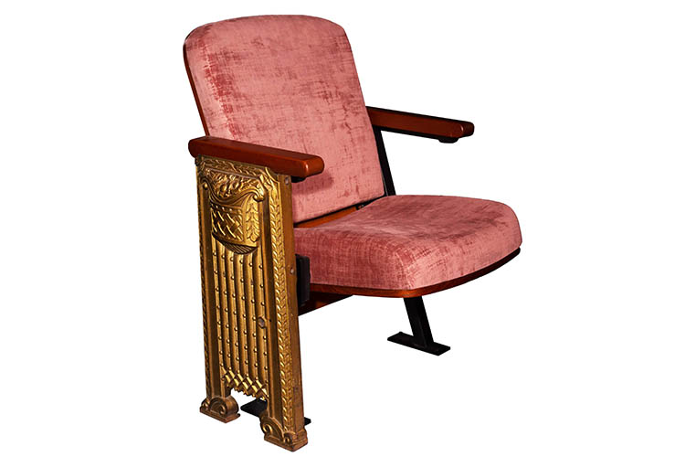 New theater seat with red cushion and gold gilded chair arm.