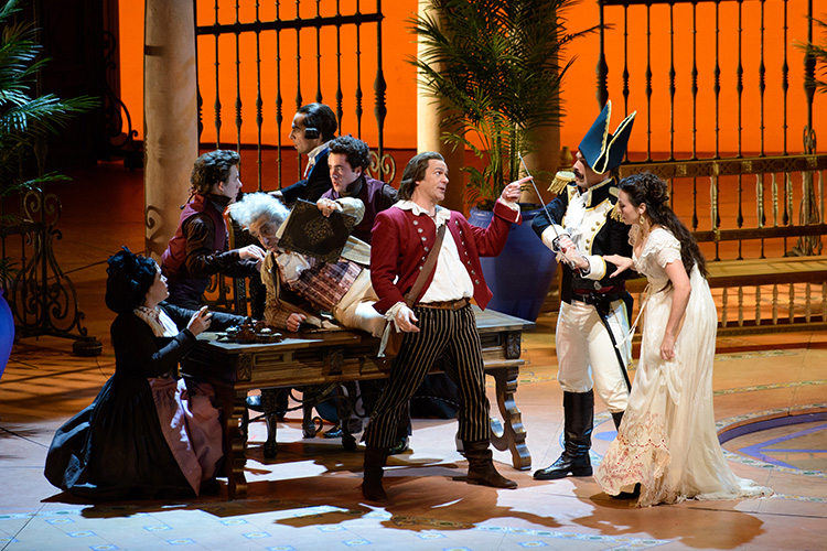 A man with ponytail wearing a read jacket, and stripped pants performing in The Barber of Seville.