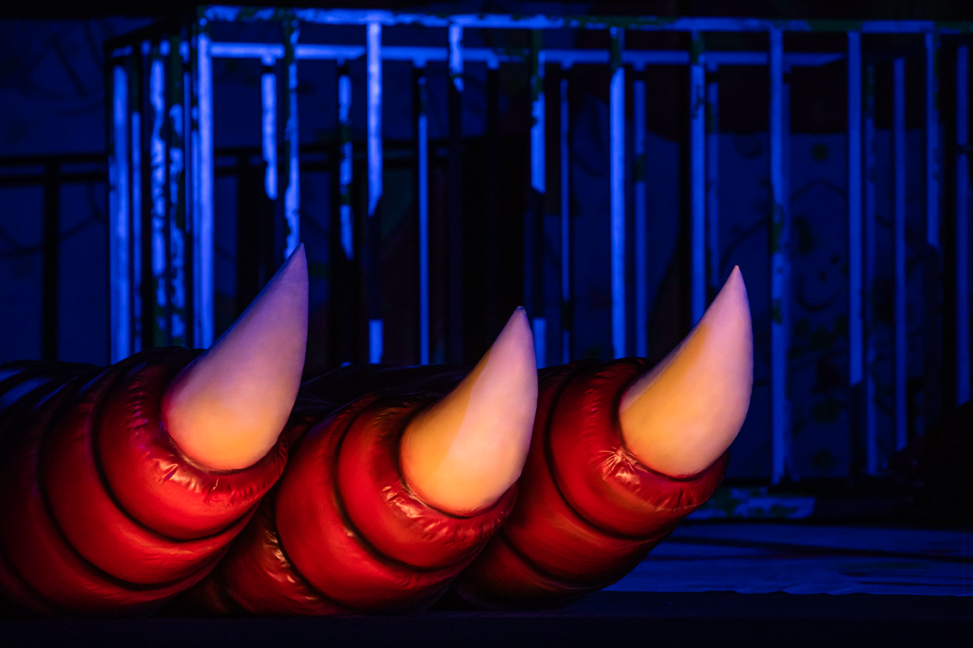 Red dragon claw reaching under stage curtain